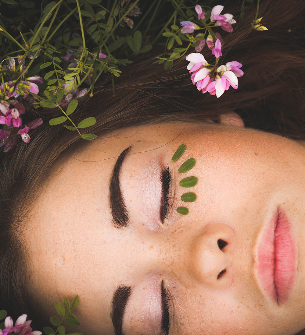 woman relaxing with healthy skin and flowers